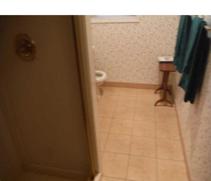 Water damaged bathroom in need of floor removal and dry down services.