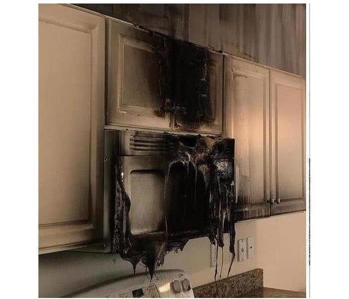 completely melted microwave and smoke damage in white kitchen