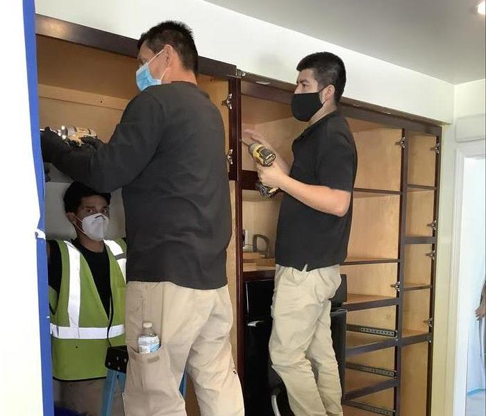 2 SERVPRO employees disassembling a cabinet